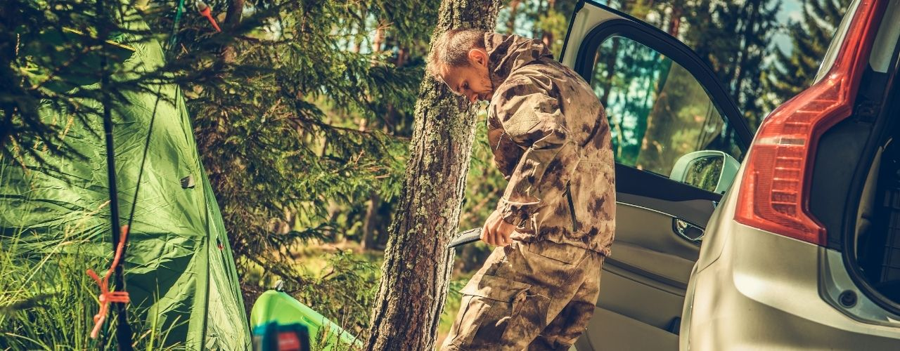 Man wearing a camo suit camping in the woods.